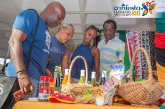 Patrons admiring Guyanese products on display at the Guyana Booth at the CARIFESTA Grand Market