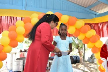 Mrs. Sita Nagamootoo makes a presentation to one of the children attending the function