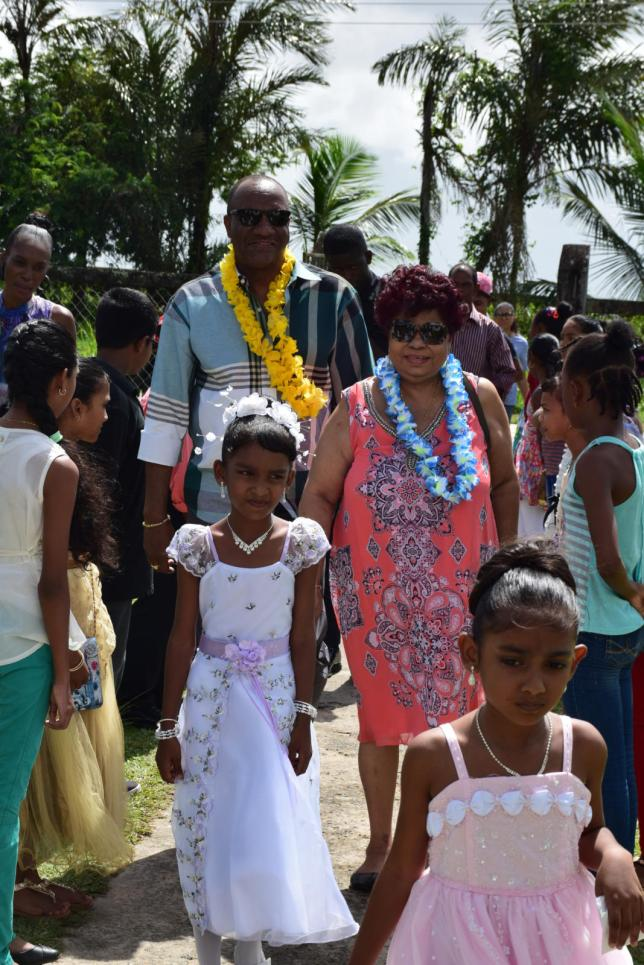 Minister of State, Joseph Harmon and Minister of Social Protection, Amna Ally as they were greeted by the children at the Maryville Primary School, Leguan