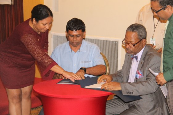 Dr. Paloma Mohamed, Deputy Vice-Chancellor for Philanthropy, Alumni and Civic Engagement, University of Guyana, assists Ragindra Persaud, Chief Executive Officer, NPGC and Professor Ivelaw Griffith, Vice-Chancellor, University of Guyana with the MoU documents to be signed