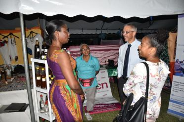 Minister of Business Dominic Gaskin interacting with local entrepreneurs and representatives from local businesses about their products at the Essequibo Agro and Trade Expo