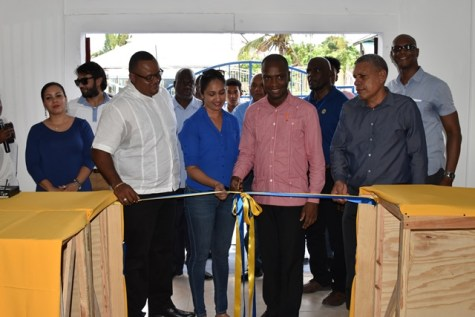 Bartica Mayor Gifford Marshall cuts the ribbon to the new Ansa McAl location, while Regional Chairman Gordon Bradford (right) and Ansa McAl Managing Director Troy Cadogan looks on