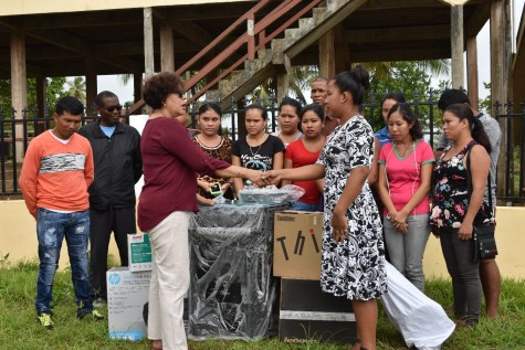 Minister within the Ministry of Indigenous Peoples' Affairs Valerie Garrido-Lowe (left) handing over the equipment to HEYS participants of Hosororo