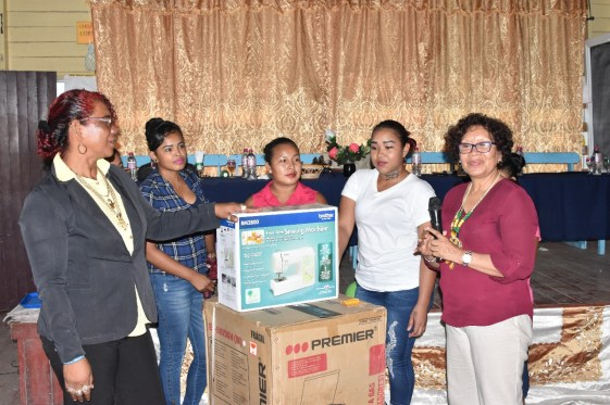 Minister within the Ministry of Indigenous Peoples' Affairs Valerie Garrido-Lowe (left) handing over the equipment to Chairperson of Canal Bank, Stephanie Miguel and HEYS participants