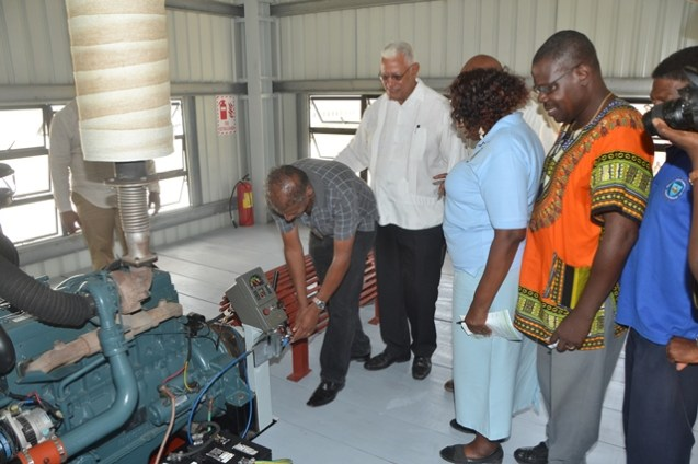 Minister of Agriculture, Noel Holder, RDC Chairperson, Genevieve Allen, Finance Secretary, Hector Butts (partly hidden) and NDC Chairman, Forbes Abrams examining the pump
