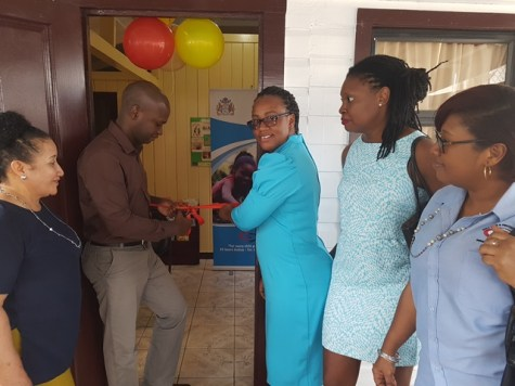 Mayor Gifford Marshall cuts the ribbon to officially launch the Children's Advocacy Centre while representatives of the Ministry of Social Protection, Unicef and Blossom Inc observe in Bartica, Region 7