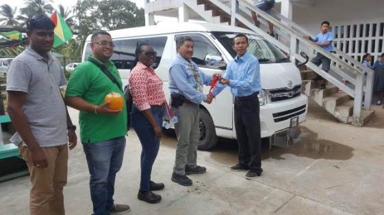 Minister of Indigenous People's Affairs, Sydney Allicock presents the key to the school bus to Headmaster Glynn De LaCruz, looking are Deputy Permanent Secretary, Sherry Samantha Fidee and other officials.