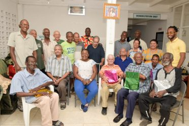 Minister within the Ministry of Natural Resources Simona Broomes shares a photo-op with the men of the St Thomas More Home
