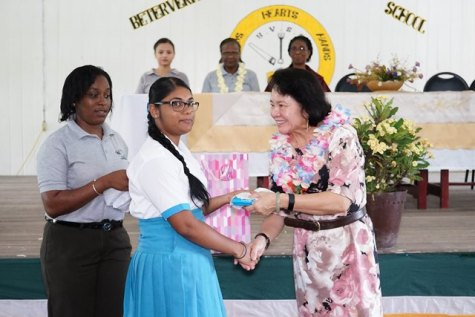 First Lady Sandra Granger handing over a gift to one of the students of Beterverwagting Secondary School, compliments of B and J Civil Works.