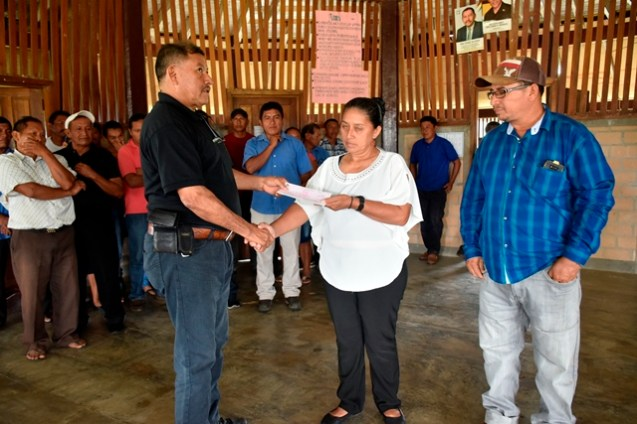 Jackie Allicock, Senior Councillor, Surama Village receiving a cheque from Minister of Indigenous Peoples' Affairs, Sydney Allicock in the presence of Permanent Secretary, Alfred King.