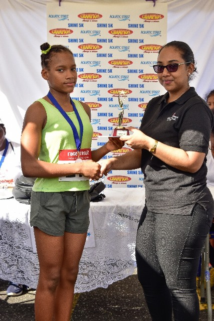 Aliza Persaud receiving her first-place trophy.