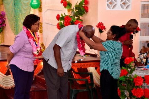 Minister of Public Telecommunications, Catherine Hughes watches on as Chairman, National Data Management Authority, Floyd Levi receives his medal of appreciation.