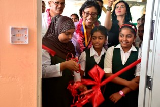 Minister of Public Telecommunications, Catherine Hughes beams as a student cuts the ribbon to officially open the Black Bush Polder ICT hub.