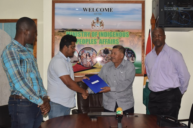 Minister hands over the contract to the representative of Sattaur Mohammed and Sons Construction.