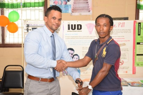 Dennis Gomes, youngest father receives hamper from the Coordinator of the Men's Health Unit of the Ministry of Public Health, Dr. Dennis Bassier.