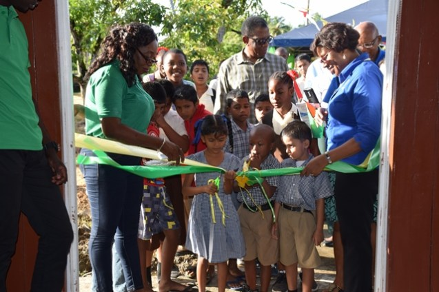 Minister of Public Telecommunications, Catherine Hughes and Chairperson, Cane Grove Community Development Council, Donette Adams watches as a pupil of the Virginia Nursery cuts the ribbon.