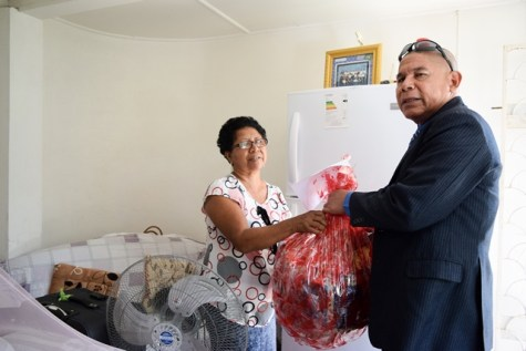 Minister of Social Cohesion with responsibility for Culture, Youth and Sport Dr. George Norton handing over the hamper to Stoby's mother Joanie James.