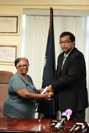 Chandra Barron, the mother of 40-year-old Sunil Ramoutar, receives her cheque.