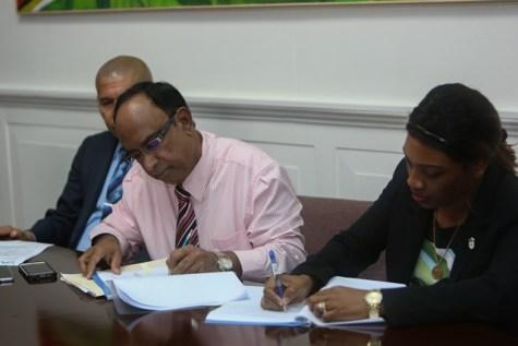 Guyana Amazon Warriors Operation Manager Omar Khan and Permanent Secretary to the Ministry Melissa Tucker inking the Memorandum of Understanding.