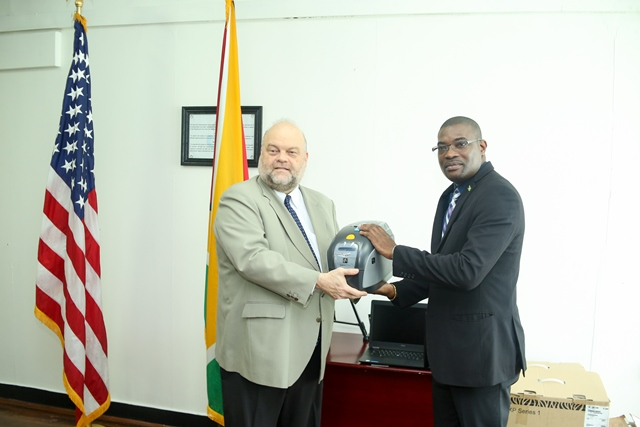 US Ambassador to Guyana, Perry Holloway presents Minister of Public Infrastructure, David Patterson with the equipment.