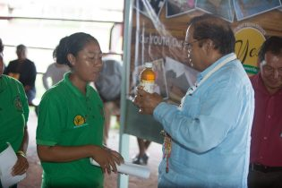 One of the Davis sisters presented a bottle of their honey to Prime Minister and Acting President, Moses Nagamootoo