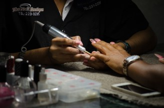 One of the employees at Urban Oasis Beauty Salon and Cosmetology School doing acrylic and nail designs on a customer.