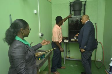 General Manager of the Guyana Gold Board, Eondrene Thompson, showing Minister of Natural Resources, Raphael Trotman, the new burning room