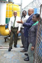 Minister Trotman, Chairman of the Board Gabriel Lall and General Manager Thompson examine the mercury control equipment