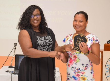Minister within the Ministry of Public Health, Dr. Karen Cummings hands over a plaque to Community Health Worker of Region One, Patricia Fancis in recognition of outstanding work.