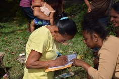 AREO Leola Narine assists resident with signing