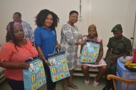 Hampers being handed over by Minister of Public Health, Volda Lawrence and GPHC staff to Mandisa McKinnon and Delroy George, mother and father of triplets.