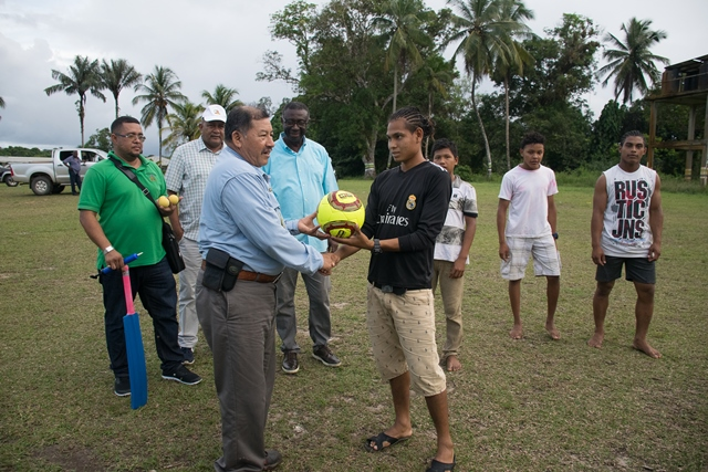 Minister of Indigenous Peoples' Affairs, Sydney Allicock handing over sport gear to the youths at Tapakuma.