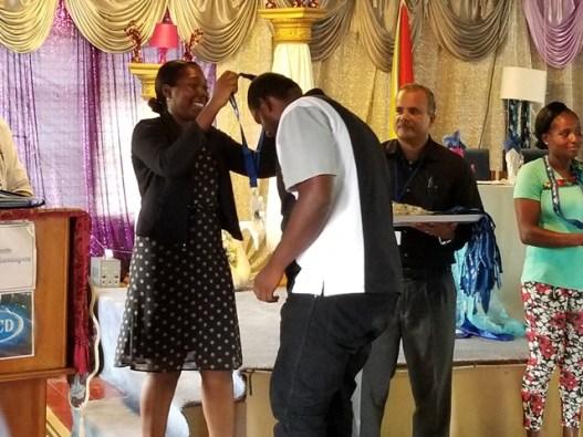Andrea Benjamin presenting a key to one family member