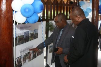 Minister of State Joseph Harmon and General Manager DHB Rawlston Adams view some photos on display at the Umana Yana