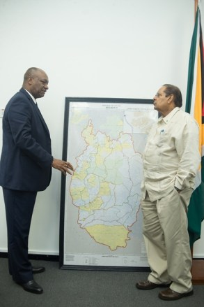 Minister of State Joseph Harmon briefs Prime Minister Moses Nagamootoo.