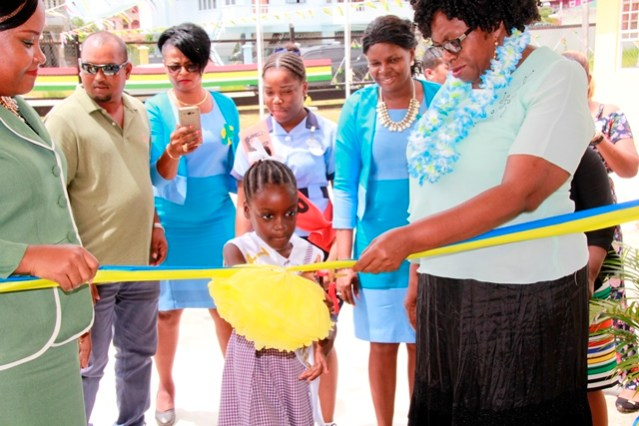 RDC Region Four Chairwoman, Ms. Genevieve Allen (right) and Assistant Chief Education Officer (Nursery) ag, Ms. Samantha Williams (left) and a student of the school conducting the ceremonial cutting of the ribbon.