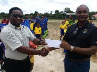 Sports Officer, Mark Ambrose receiving third-place prize money from GFF President Wayne Forde on behalf of Rivers View FC.