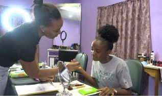 Makeup Artist and Owner of Sunkissed Artistry, Mosa Henry assisting one of her students at the beginner's course makeup class