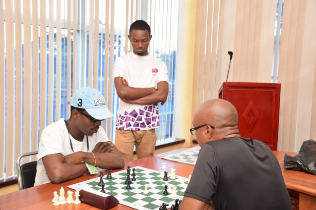 Team Captain [wearing hat] Wendell Meusa in deep concentration during a game of chess