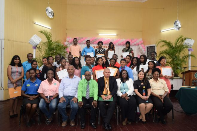 [seated] Minister of Culture, Youth and Sport, Dr. George Norton [fourth right], Youth Director, Melissa Carmichael [third right], Senior Economic Empowerment Officer, Samuel Saul [fourth left], Acting CEO of GSA, Dr. Dexter Allen [third left] flanked by students from the graduating class