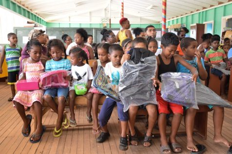 Students showing off their new school supplies in Ituni
