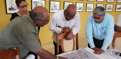 Finance Minister Winston Jordan and DDL Chairman Komal Samaroo listen as DDL Projects Manager Kenneth Ragnauth explains the layout of new facilities in the DDL expansion programme