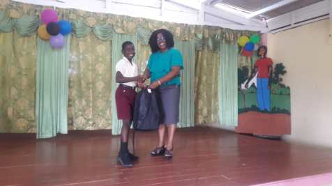 Minister within the Ministry of Public Health, Dr. Karen Cummings handing a bursary to Darion Peters who topped the village with 490 marks