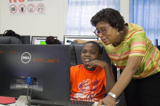 Minister of Public Telecommunications, Catherine Hughes interacting with a participant of the coding camp