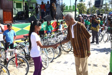 President David Granger hands over one of the bicycles to one of the beneficiaries