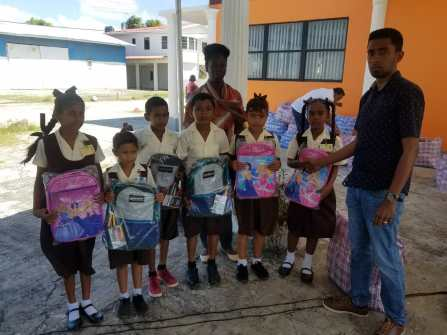 Representative from the Region Three Private Sector Association handing over backpacks to lucky students as their class teachers looks on
