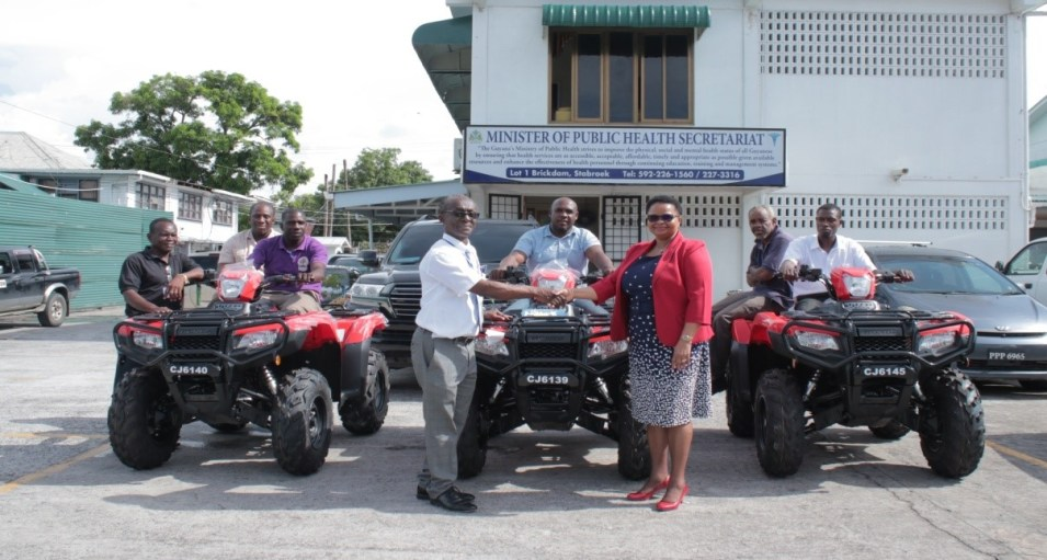 In this Aubrey Odle photo, PAHO/WHO Representative Dr William Adu-Krow and Minister Volda Lawrence shake hands after the handing over ceremony of the ATVs on the MOPH premises