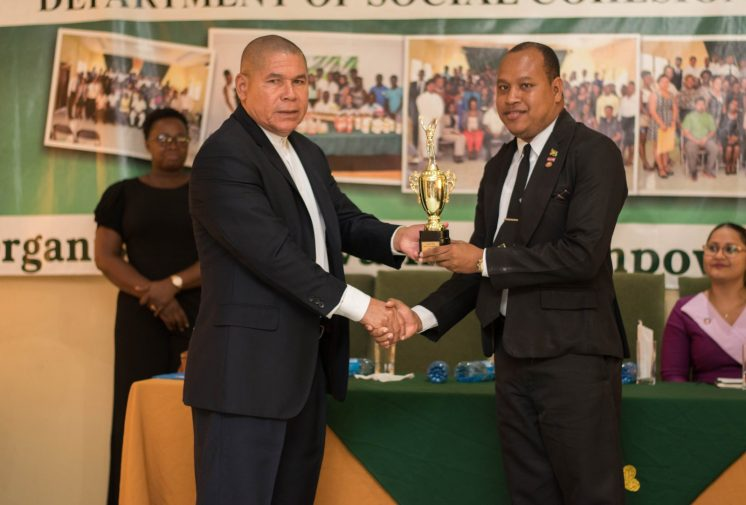 Lauristan Chow receiving his award for 'Leadership Best Exemplified' from Minister of Social Cohesion Dr. George Norton