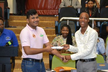 Shemar Davis receiving his scholarship from a representative of Global Technology