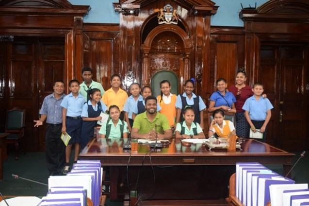 Students and teachers of the Hinterland Regions with Public Relations Officer, Yannick December and Shavon Joseph, staff of Ministry of Indigenous People's Affairs in the National Assembly room.